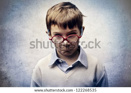 Angry child with red glasses - stock photo