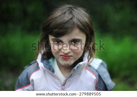 Angry child. Young girl making funny grimace face on a green background.. - stock photo