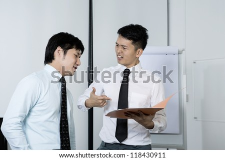 Angry Chinese business men looking at a report