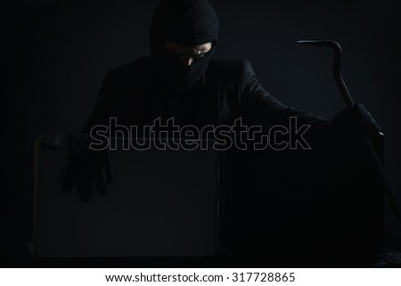 Angry computer hacker in suit stealing data from laptop with crowbar and gloves in front of black background  - stock photo