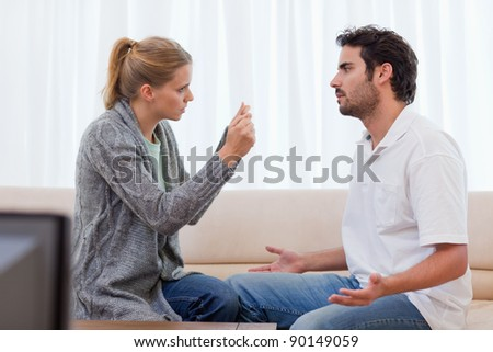 Angry couple arguing in their living room - stock photo