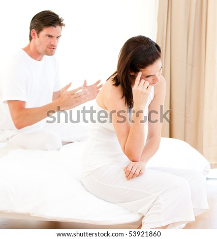 Angry couple having an argument sitting on their bed