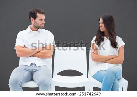 Angry couple not talking after argument against grey - stock photo