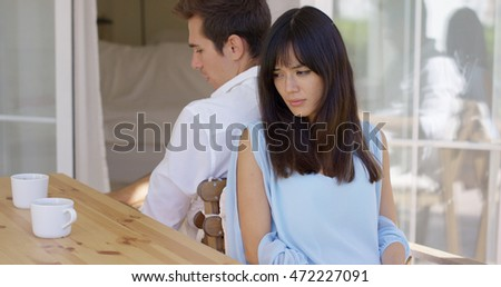 Angry couple sitting back to back at table