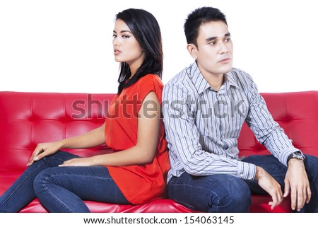 Angry couple sitting back to back on the red sofa over white background - stock photo