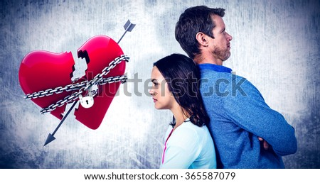 Angry couple standing back to back against locked heart - stock photo