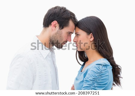 Angry couple staring at each other on white background - stock photo