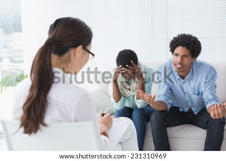 Angry couple talking to their therapist in therapists office - stock photo