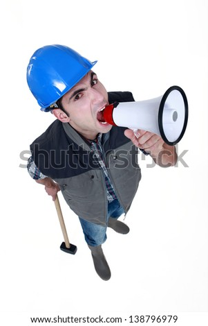 angry craftsman shouting through a megaphone - stock photo