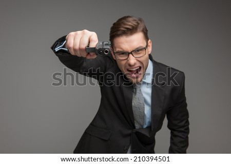 Angry criminal businessman with gun on grey background. angry boss shouting at camera and aiming gun