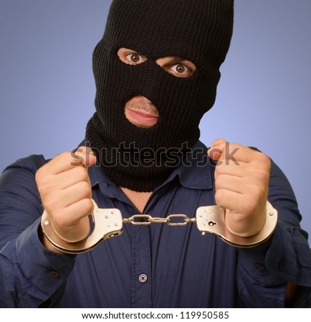angry criminal man locked in handcuffs isolated on colored background