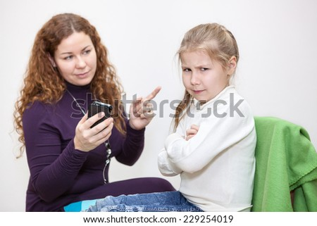 Angry daughter sitting after mother taking her the cellphone - stock photo