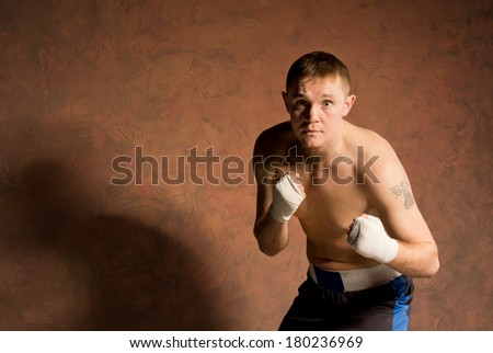 Angry determined young boxer crouching forwards with his eyes fixed on his opponent on a brown background with copyspace - stock photo