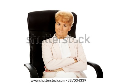 Angry elderly business woman sitting on armchair with folded arms - stock photo