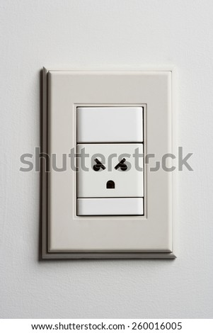 Angry Electric Wall Power Outlet on a White Wall. Outlet Expression Looks like It's Angry - stock photo