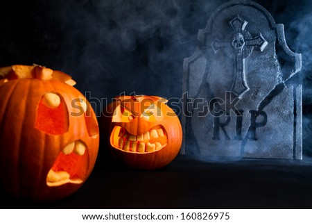 Angry face and scared face of Halloween pumpkins with tombstone on misty dark background. - stock photo