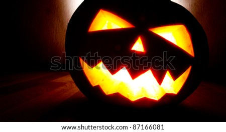 Angry face of helloween pumpkin at black background - stock photo