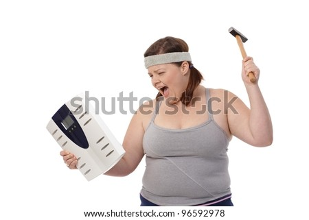Angry fat woman punching scale by hammer, shouting.? - stock photo
