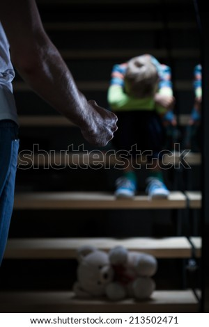 Angry father and scared boy at night - stock photo