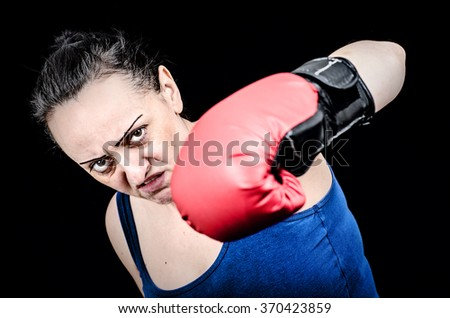 Angry female boxer throwing punch. Black background - stock photo