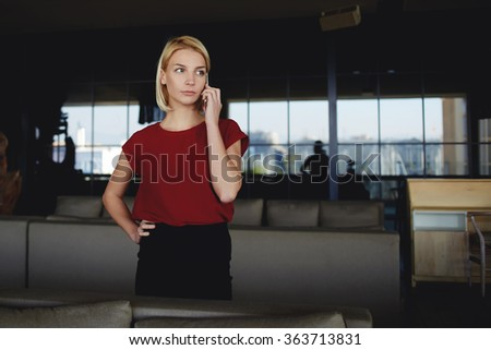 Angry female CEO dressed in formal wear calling with mobile phone to her colleagues which are late for a meeting, unmet businesswoman listening by cell telephone negative comment about last project - stock photo