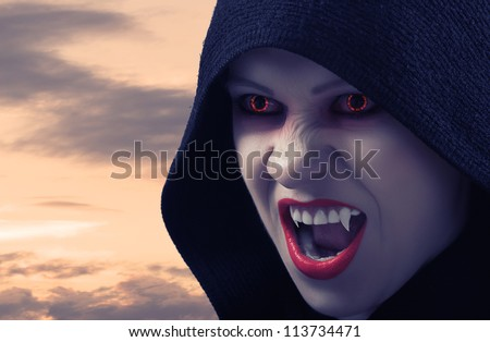 angry female vampire at sunset and moon - stock photo