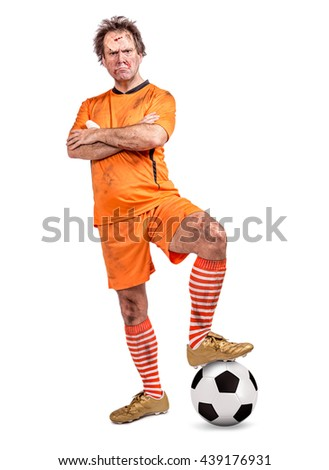 Angry football player posing with ball isolated on white background. Angry man in clothes soccer player standing with ball. Dirty footballer with ball. Injured football player with ball