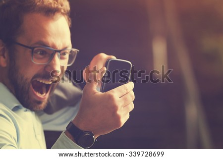 Angry gay biting the phone. - stock photo