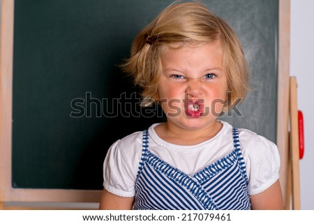 angry girl in front of black board  - stock photo
