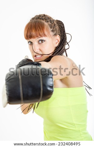 Angry girl in rage wearing boxing gloves ready to fight and punching or hitting camera or you. Strength, power or competition concept image of beautiful young caucasian woman isolated on white - stock photo