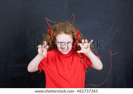 Angry girl in red t-shirt stand near horns and devil tail hand drawing on blackboard. Child character. Health and medical concept.