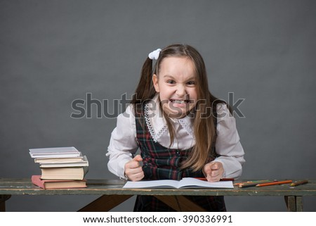 Angry girl in school uniform pounding his fists on the table with books - stock photo