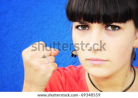Angry girl showing fist - stock photo