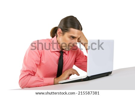 Angry grumpy Young handsome man with mobile phone, with laptop, looking at the monitor over white background