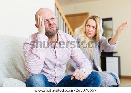 Angry guy and woman during quarrel in living room at home  - stock photo