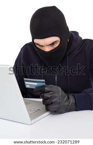 Angry hacker using laptop and credit card on white background - stock photo