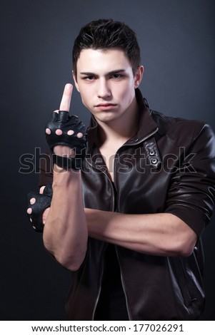 Angry handsome young man is showing a middle finger isolated on a black background - stock photo