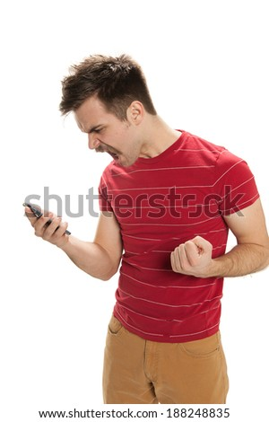 Angry, handsome young man looks down at his phone and screams in anger, his other hand balled into a fist, isolated on white