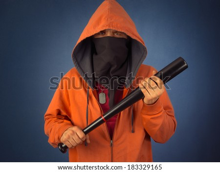 Angry hooligan in the mask and hoody holds baseball bat - stock photo