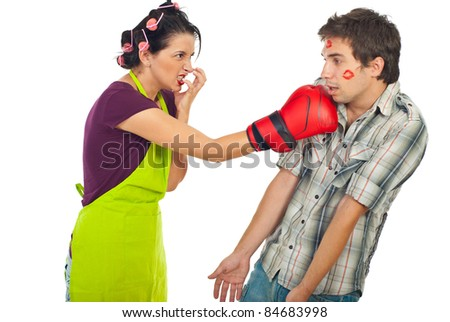 Angry housewife kicking with boxing glove her drunk unfaithful husband isolated on white background - stock photo