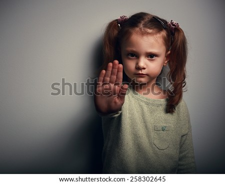Angry kid girl showing hand signaling to stop useful to campaign against violence and pain on dark background. Closeup portrait
