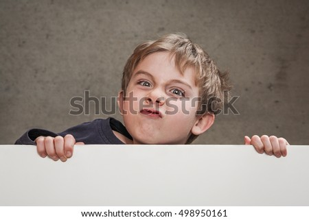 Angry kid looking over a blank sign