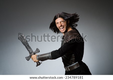 Angry knight with sword against dark background - stock photo