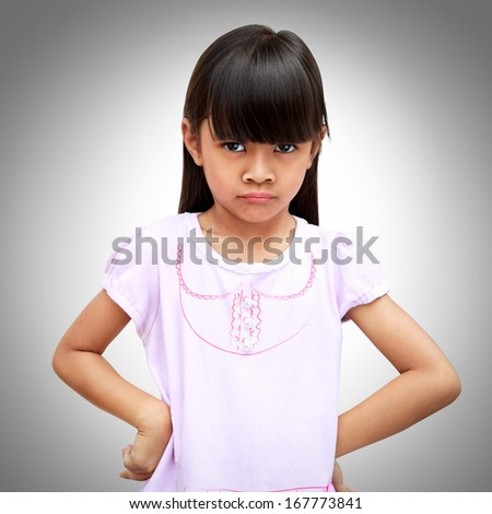 Angry little asian girl on a grey background - stock photo
