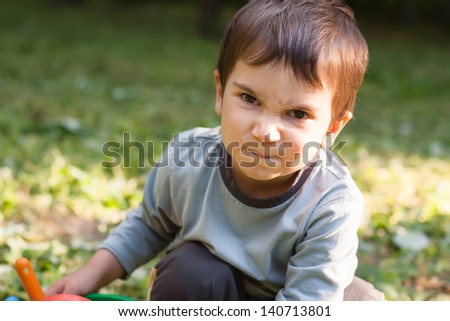Angry little boy. Focus primarily on the eyes - stock photo