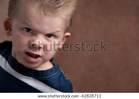 Angry little boy glaring at the camera on a brown textured background