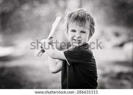 Angry little boy, holding sword, glaring with a mad face at the camera, outdoors in the park, monochrome conversion - stock photo