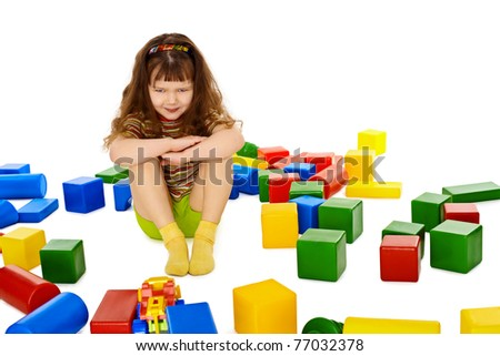 Angry little girl among the scattered toys isolated on white background - stock photo