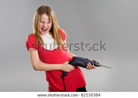 Angry little girl holding electric drill - stock photo