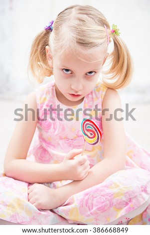angry little girl wit sugar candy - stock photo